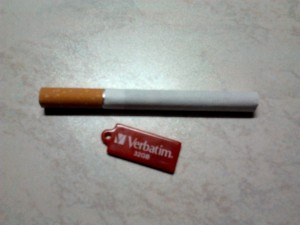 Pendrive with fast transfer speed size compared next to a cigarette
